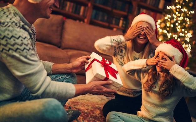 즐거운 성탄절 보내시고 새해 복 많이 받으세요! 행복한 가족은 서로 선물을 교환하는 산타클로스 모자를 쓰고 새해를 기다리고 있습니다.