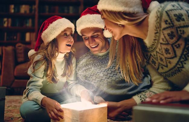 С новым годом и рождеством! счастливая семья ждет новый год в шапках санта-клауса. родители преподносят подарочную коробку своей очаровательной дочери. волшебный свет изнутри.