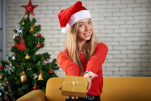 Веселого рождества и счастливого нового года, красивая белая кавказская женщина празднует, обменивается подарками, расслабляется перед желтым диваном и рождественской елкой в комнате