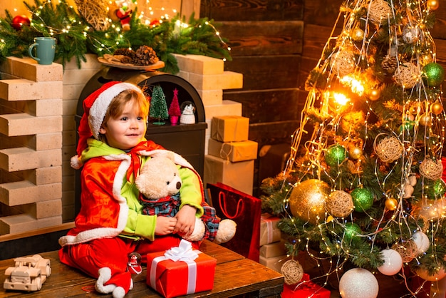 メリークリスマス、そしてハッピーニューイヤー。子供は家で冬休みを楽しんでいます。家族の日のクリスマス。喜びと愛に満ちた家。かわいい小さな男の子はクリスマスツリーの近くで遊ぶ。贈り物と驚き。