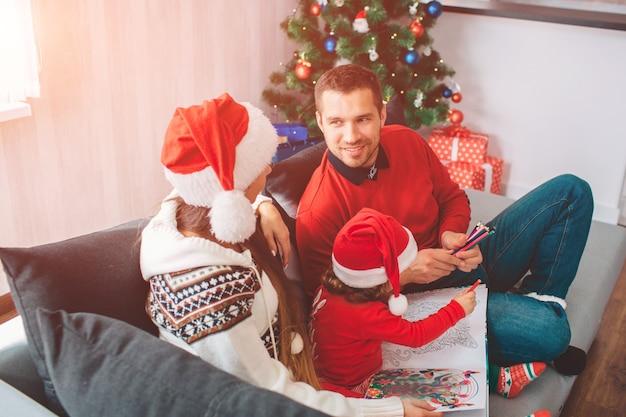 メリークリスマス、そしてハッピーニューイヤー。ソファに一緒に座っている家族の素敵な写真。親はお互いを見つめます。女性は帽子をかぶっています。若い男は微笑む。彼らの娘は色で描いています。