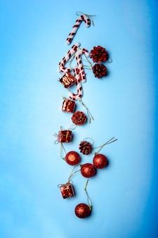 Счастливого рождества и счастливого нового года на синем фоне. новогодние шары и конфета