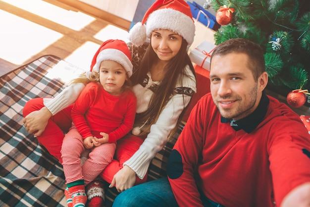 メリークリスマス、そしてハッピーニューイヤー。素敵な家族の写真。若い男はカメラを持って自分撮りをします。それらのすべてがポーズします。子供は真面目そうだ。
