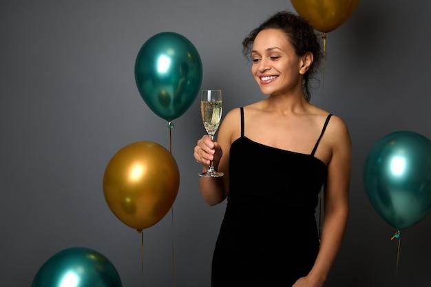 즐거운 성탄절 보내시고 새해 복 많이 받으세요. 반짝이는 금색과 녹색 금속 풍선이 있는 회색 배경에 샴페인 한 잔을 들고 이브닝 드레스를 입은 아름다운 히스패닉 여성의 홍보 사진