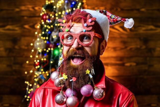 メリークリスマス、そしてハッピーニューイヤー。クリスマスバッグを持って家にいるサンタ。明けましておめでとうございます。あごひげを生やした男