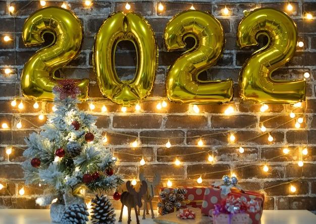 즐거운 성탄절과 새해 복 많이 받으세요, 크리스마스 선물이 있는 테이블 위의 작은 크리스마스 트리와 2022년에는 황금색 풍선 숫자가 있습니다. 벽돌 벽 배경