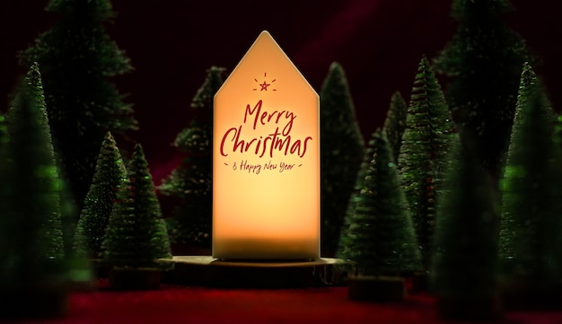 С рождеством и новым годом текст на домашней лампе с рождественской елкой на столе из красной бархатной ткани в темном ночном настроении Premium Фотографии