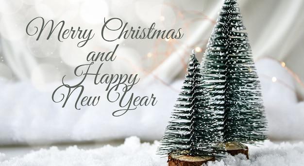 기쁜 성 탄과 새 해 복 많이 받으세요 텍스트 샴페인 색 실크 배경과 하얀 눈에 두 개의 크리스마스 나무. 트렌디한 장식. 새 해 개념입니다. 인사말 카드. 전나무 나무와 크리스마스 배경입니다.