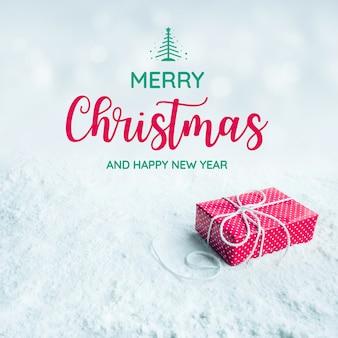 メリークリスマスと新年のテキスト、ギフトボックス、雪の背景に存在します。