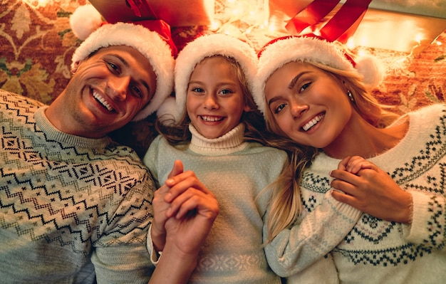 Веселого рождества и счастливого нового года! вид сверху счастливой семьи лежит на полу с подарочными коробками и гирляндой рядом.