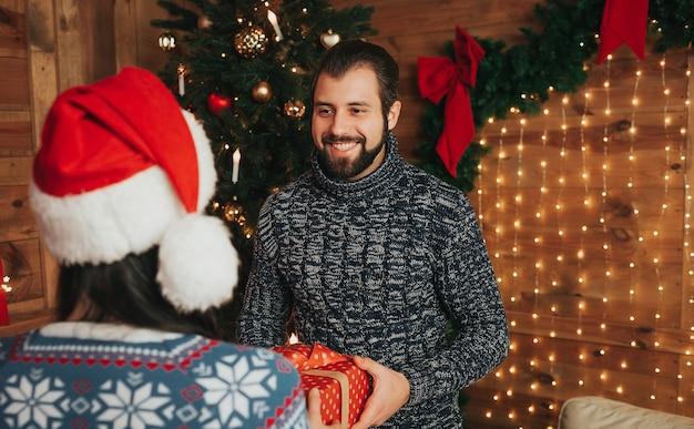 メリークリスマス、そしてハッピーニューイヤー 。家で休日を祝う若いカップル。幸せな若い男と女がお互いに贈り物をします。