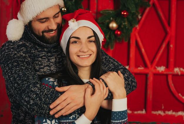 メリークリスマス、そしてハッピーニューイヤー 。若いカップルが自宅で休日を祝います。幸せな若い男と女が抱擁し、お互いに贈り物を与える