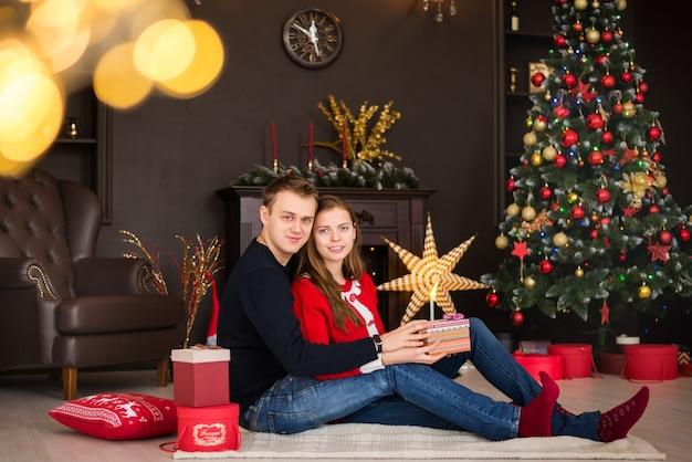 Веселого рождества и счастливого нового года!. молодая пара празднует праздник дома. мужчина и женщина распаковывают подарки