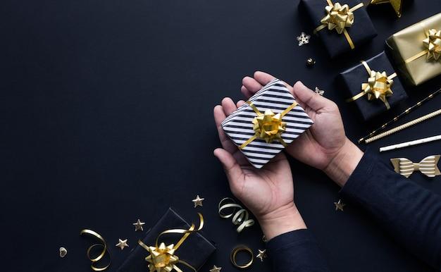 暗い背景に金色のギフトボックスと飾りを持っている人の手でメリークリスマスと新年のお祝いのコンセプト。冬の季節と記念日