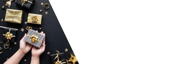 暗い上に金色のギフトボックスと飾りを手に持っている人とメリークリスマスと新年のお祝いの概念