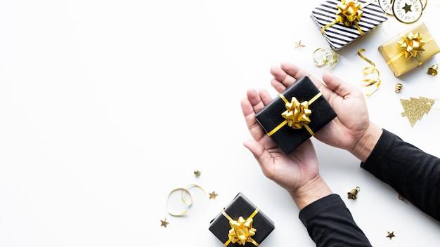 メリークリスマスと新年のお祝いのコンセプトは、白い背景に金色のギフトボックスと飾りを手に持っています。冬の季節と記念日