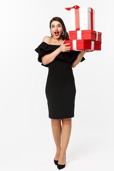 메리 크리스마스와 새 해 휴일 개념입니다. 크리스마스 선물을 들고 웃 고, 흰색 배경 위에 서있는 검은 드레스에 쾌활 한 아가씨.