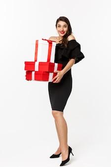 メリークリスマスと年末年始のコンセプト。興奮した若い女性は、クリスマスプレゼントを持って、カメラに微笑んで、黒いドレス、白い背景を身に着けて、贈り物を持ってきます。