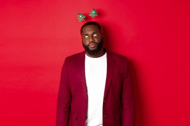 メリークリスマス。イライラするアフリカ系アメリカ人の男は、パーティーで愚かなヘッドバンドを身に着けて、赤い背景の上に立って目を転がします