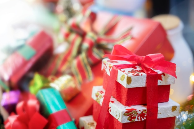 Merry christmas background concept. closeup of red gift box with blurred gift boxes in bac