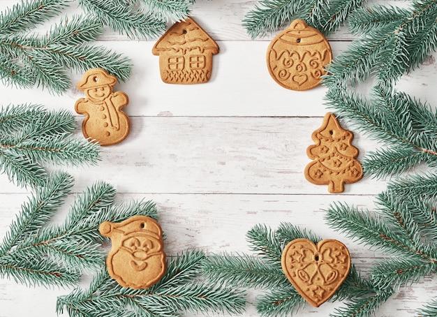 メリークリスマス背景おいしい自家製ジンジャークッキー。ベーキング、調理器具、ジンジャーブレッドを調理するための材料。幸せな新年のグリーティングカード。クリスマステーブル。モミの木、松。