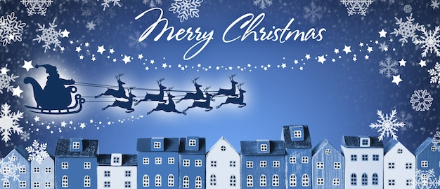 Merry christmas banner - santa claus in a sleigh and reindeer sled flies over houses of the city on blue winter background.
