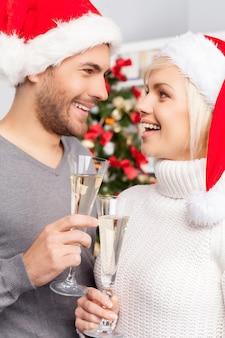 메리 크리스마스! 샴페인 피리를 들고 서로를 바라보는 아름다운 젊은 부부