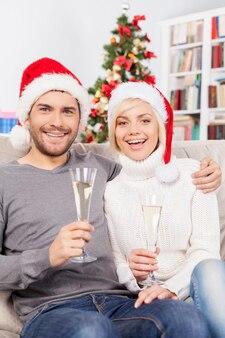 메리 크리스마스! 소파에 앉아 샴페인 피리를 들고 웃고 있는 아름다운 젊은 부부