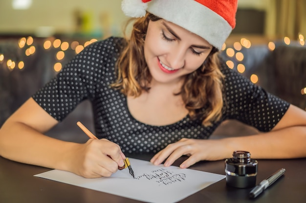 Merry christmas. calligrapher young woman writes phrase on white paper