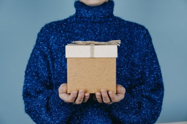メリークリスマスカードヒュー年クリスマス誕生日バナー女性の手で青いセーターを持ってクラフトギフト