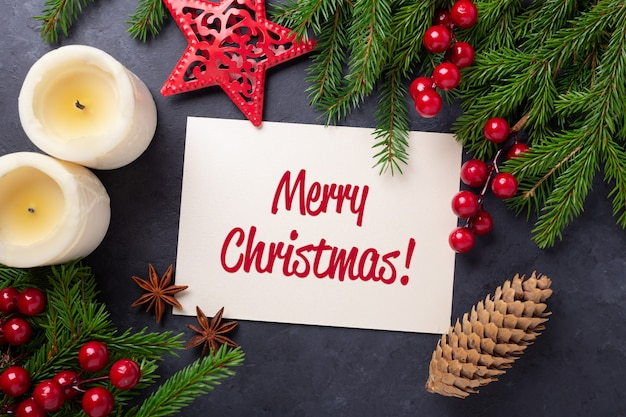 Merry christmas card with paper, gift box and fir tree branch on black background