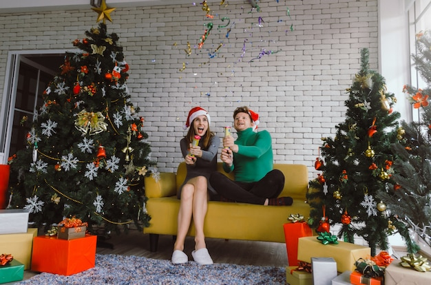 Merry christmas. caucasian sweet couple with red santa hat having fun with colorful paper