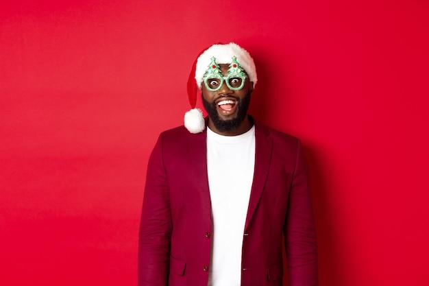 メリークリスマス。面白いパーティーグラスとサンタの帽子をかぶって、うれしそうに笑って、冬休みを祝って、赤い背景の上に立っている陽気な黒人男性。