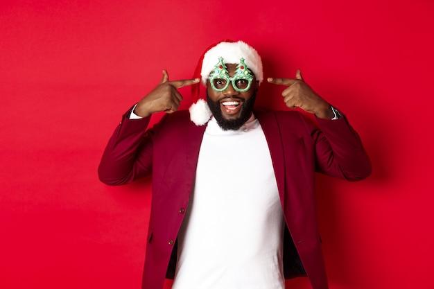 Buon natale. allegro uomo di colore che indossa occhiali da festa divertenti e cappello da babbo natale