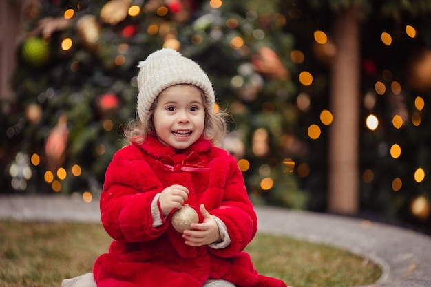 Merry christmas cheerful little girl in a red fur coat at the fair in winter