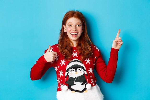 メリークリスマス。クリスマスセーターの陽気な赤毛の女の子、右上隅に人差し指、新年のプロモーションと承認の親指を示して、製品を賞賛