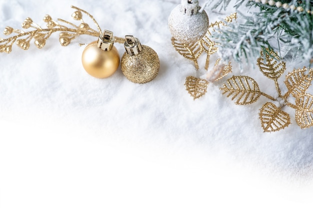 С рождеством. рождественские украшения с золотым мячом на снегу.