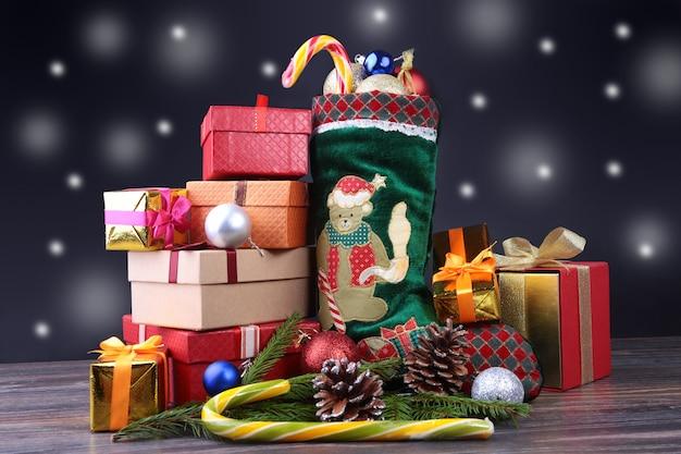 Веселая новогодняя композиция. ботинок санты с подарочными коробками на волнистых перьях со снегом и снежинками.