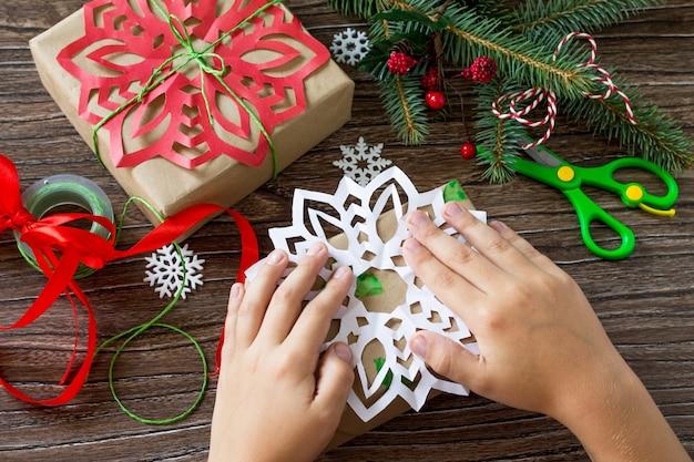 メリークリスマスのコンセプト木製テーブルの手作りボックスにクリスマスプレゼントを詰める手作り
