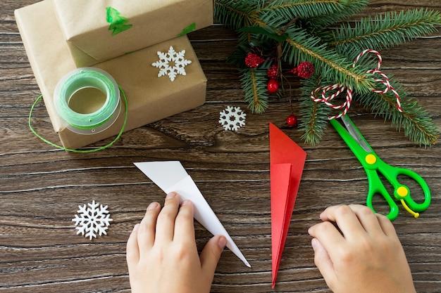 メリークリスマスのコンセプト木製テーブルの手作りボックスにクリスマスプレゼントを詰める