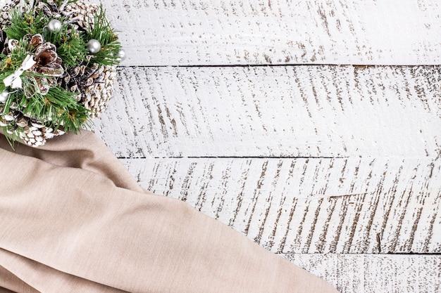 コピースペースと白い木製のテーブルの背景にコーンとベージュの布で作られた装飾的なモミの木とメリークリスマスのコンセプト。