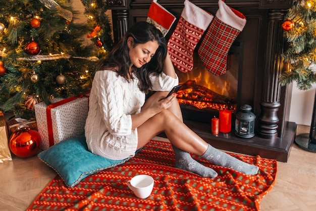Merry christmas concept. young woman sitting on the floor with mobile and writing a letter to santa claus. fireplace and xmas tree