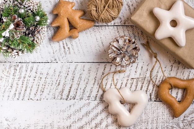 コピースペースと白い木製のテーブルの背景にギフトボックス、ペストリー、飾り要素とメリークリスマスのコンセプト