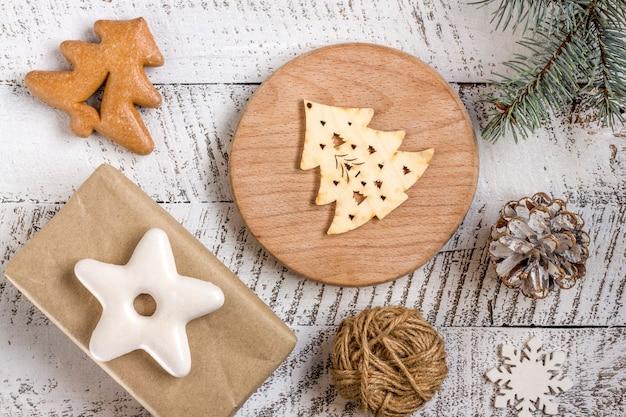 白い木製のテーブルの背景にギフトボックス、ペストリー、飾り要素とメリークリスマスのコンセプト。