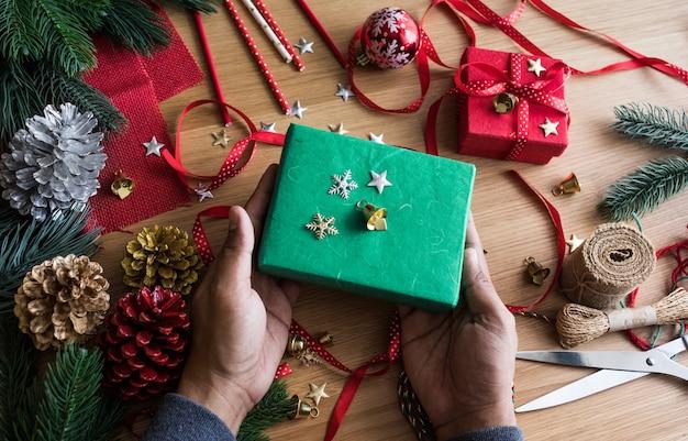 プレゼントボックスを飾る人間の手でメリークリスマスのコンセプト