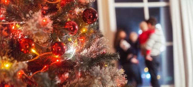 С рождеством христовым сосредоточьтесь на елке счастливая семья улыбается