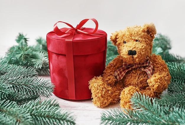 メリークリスマスギフトボックスとぬいぐるみクマのグリーティングカード。ギフト、モミの木の枝。レッドラグジュアリーニューイヤープレゼント。クリスマスのお祝い。