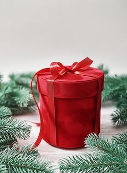 メリークリスマスギフトボックスグリーティングカード。ギフト、モミの木の枝。レッドラグジュアリーニューイヤープレゼント。クリスマスのお祝い。