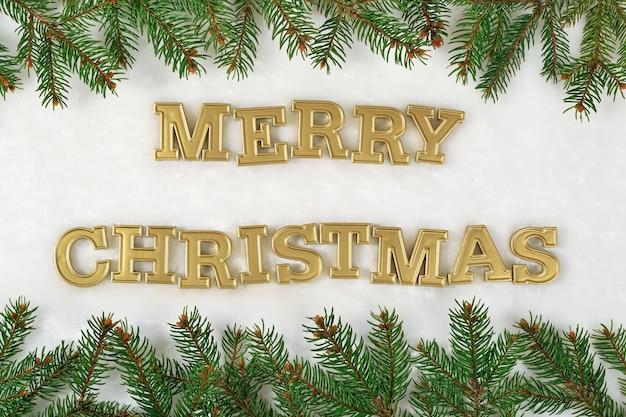 メリークリスマスの黄金のテキストと白い背景の上のトウヒの枝