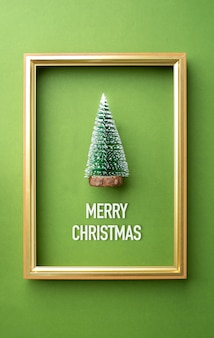 Merry christmas greeting card, green christmas tree with golden frame on green